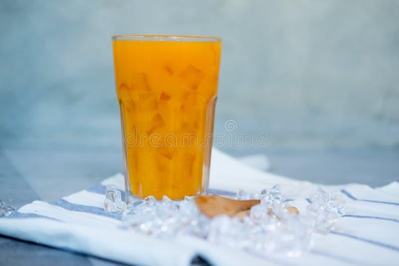 Ny orange fruktsaft med is i högväxt exponeringsglas arkivfoto