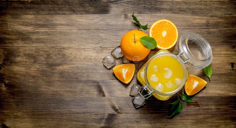 Ny orange fruktsaft med is och skivor av apelsinen arkivfoton