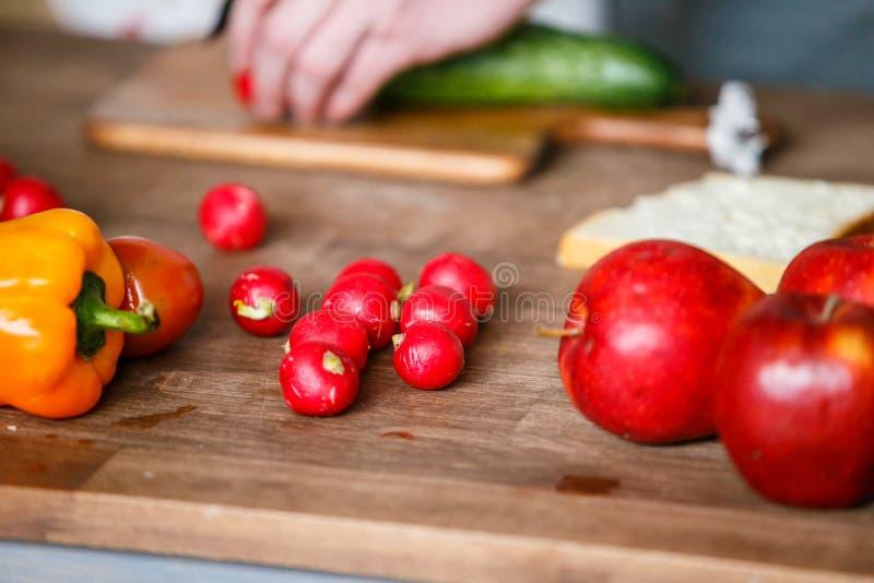 Ny orange peppar, rädisa och röda äpplen på träbrädet arkivbild