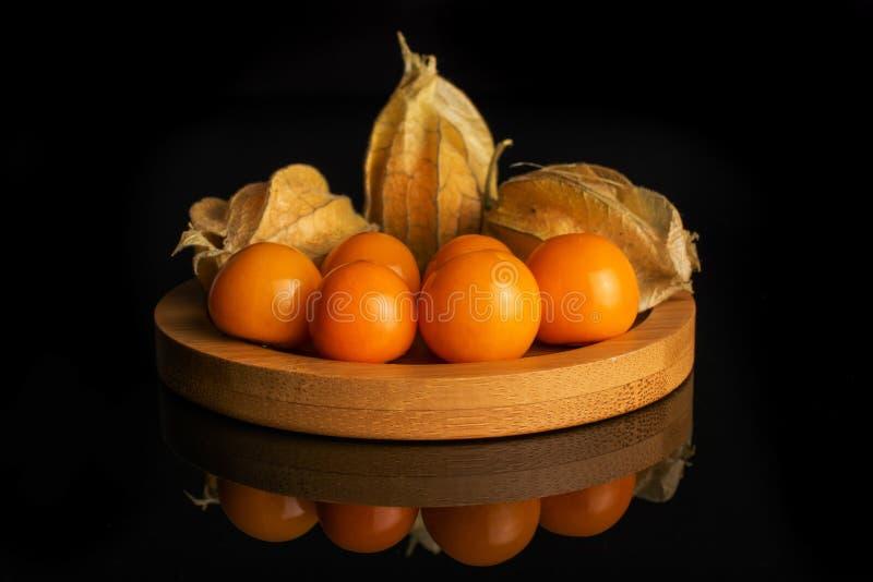 Ny orange physalis som isoleras på svart exponeringsglas royaltyfri foto