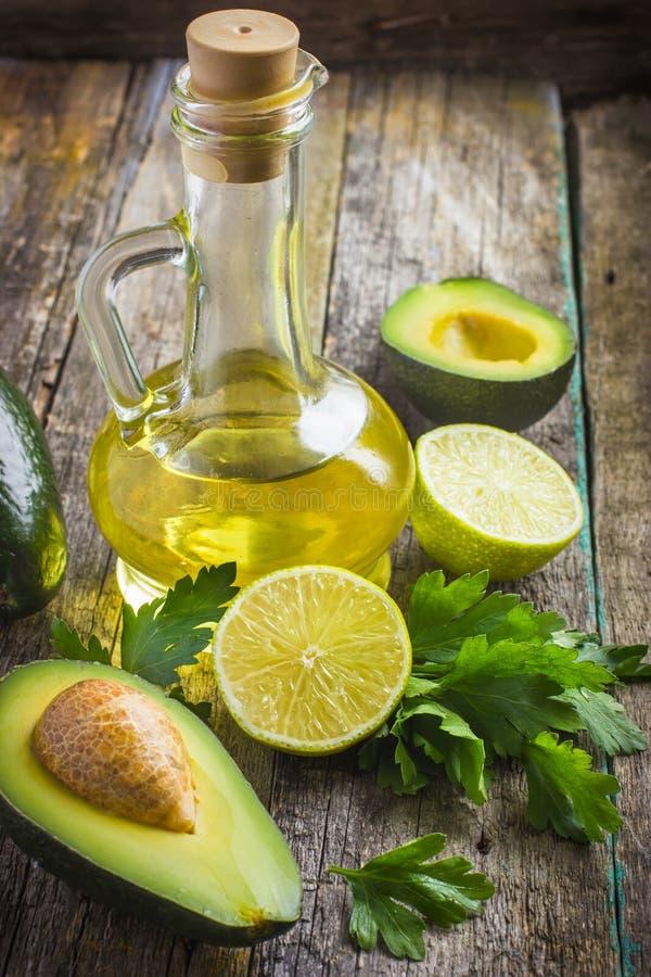 Ny organisk avokado, limefrukt, persilja och olivolja på gammalt trä royaltyfri fotografi