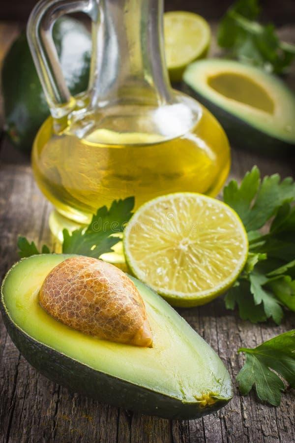 Ny organisk avokado, limefrukt, persilja och olivolja på gammalt trä royaltyfria foton