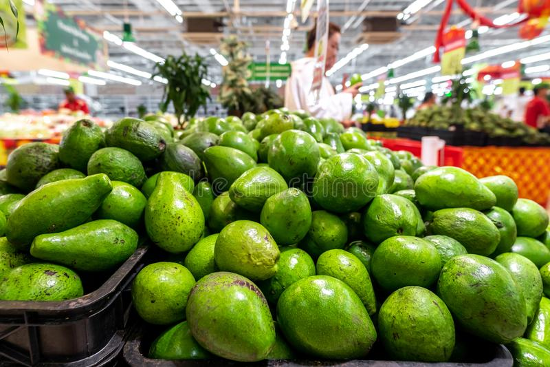 Ny organisk exotisk grön avokado på en lokal matmarknad, Bali ö Ny grön avokado på en marknadsstail arkivbilder