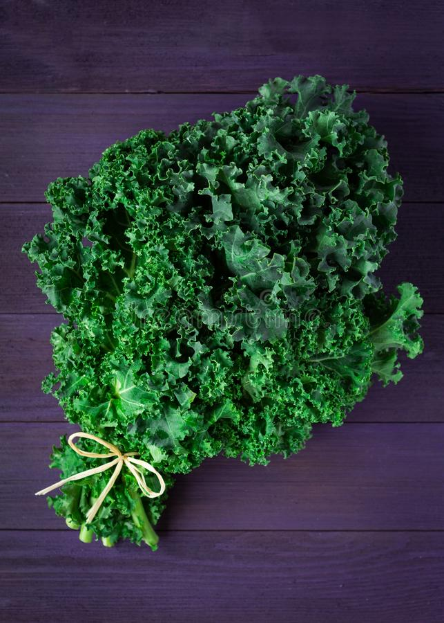 Ny organisk grön grönkål på en purpurfärgad träyttersida royaltyfria foton