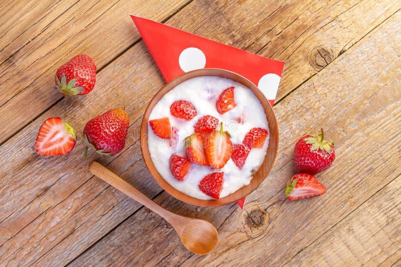 Ny organisk yoghurt med jordgubbar på trä arkivfoton