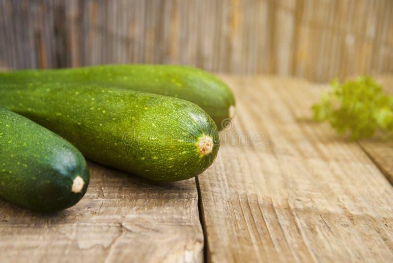 Ny organisk zucchini på lantlig träbakgrund Sommargrönsaker, utrymme för text royaltyfri foto