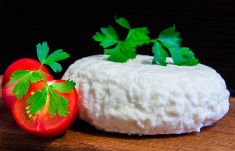 Ny ost med utmärkt smak och arom Ost på träskärbräda med tomater och nya örter royaltyfri bild