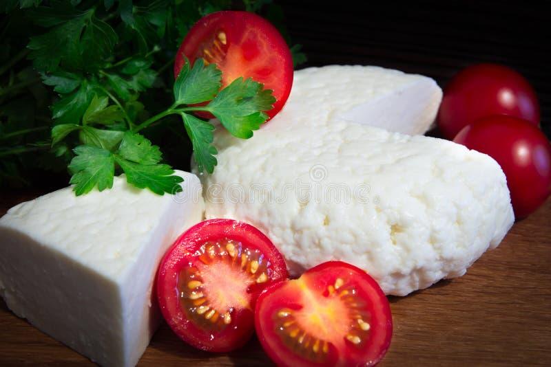 Ny ost med utmärkt smak och arom Ost på träskärbräda med tomater och nya örter royaltyfria foton