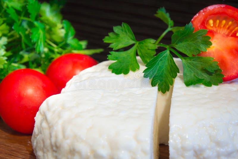 Ny ost med utmärkt smak och arom Ost på träskärbräda med tomater och nya örter arkivbilder