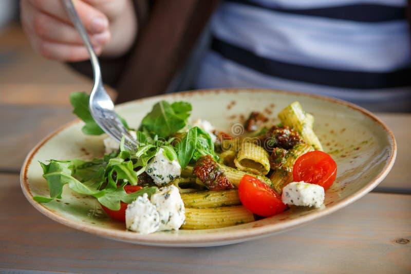 Ny pasta med den torkad tomaten, ost, rucola och pesto arkivfoto