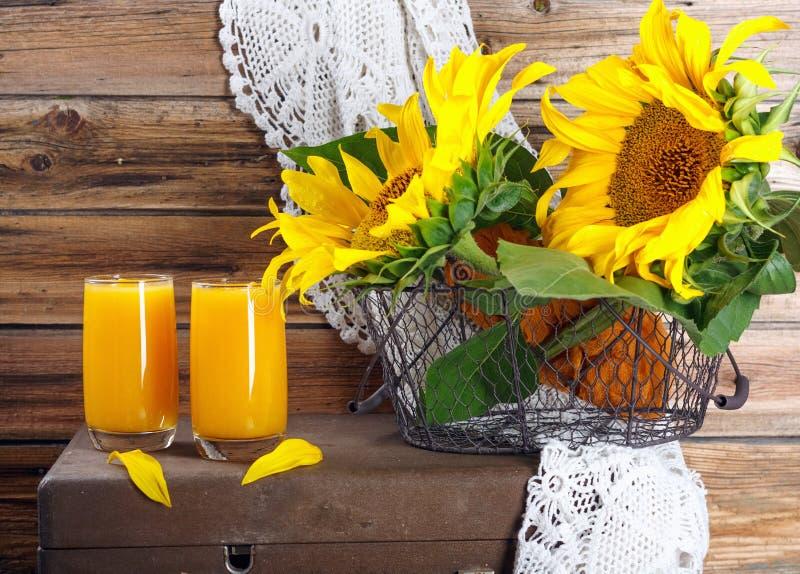 Ny pumpa och orange fruktsaft med solrosfilialer p? den gamla tr?v?ggen royaltyfri foto