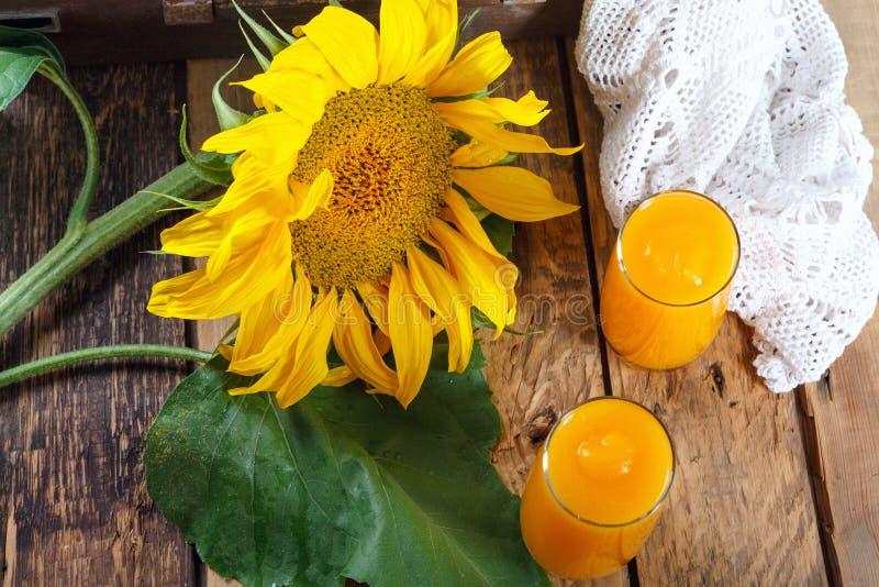 Ny pumpa och orange fruktsaft med solrosfilialer p? den gamla tr?v?ggen royaltyfria foton