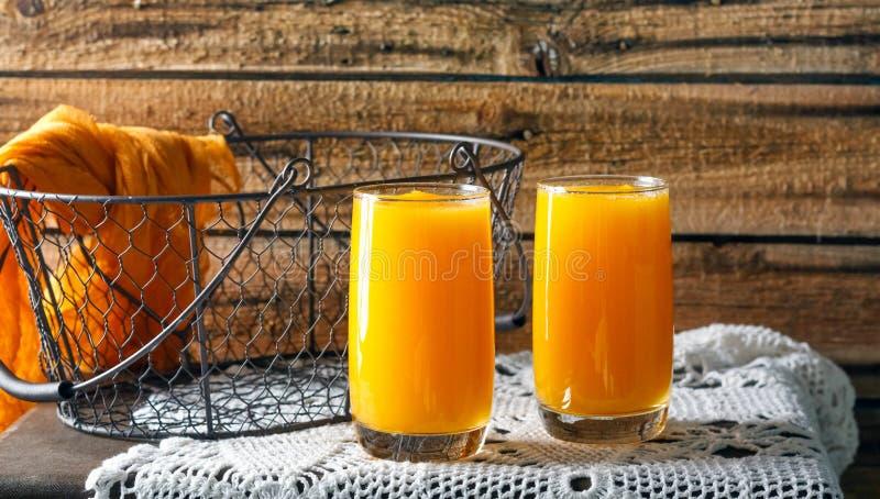 Ny pumpa och orange fruktsaft p? den gamla tr?v?ggen arkivbild