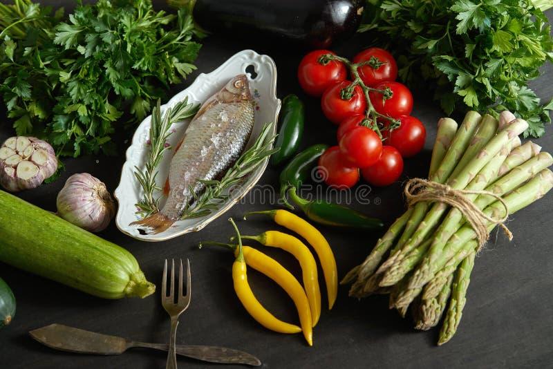 Ny rå doradafisk i en vit maträtt med en uppsättning av grönsaker på en svart tabell arkivbild