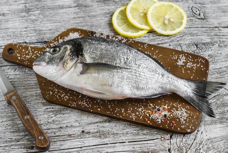 Ny rå Dorado fisk på trälantlig bakgrund fotografering för bildbyråer