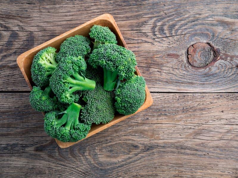 Ny rå grön broccoli i träbunke på träbakgrund, till arkivbild