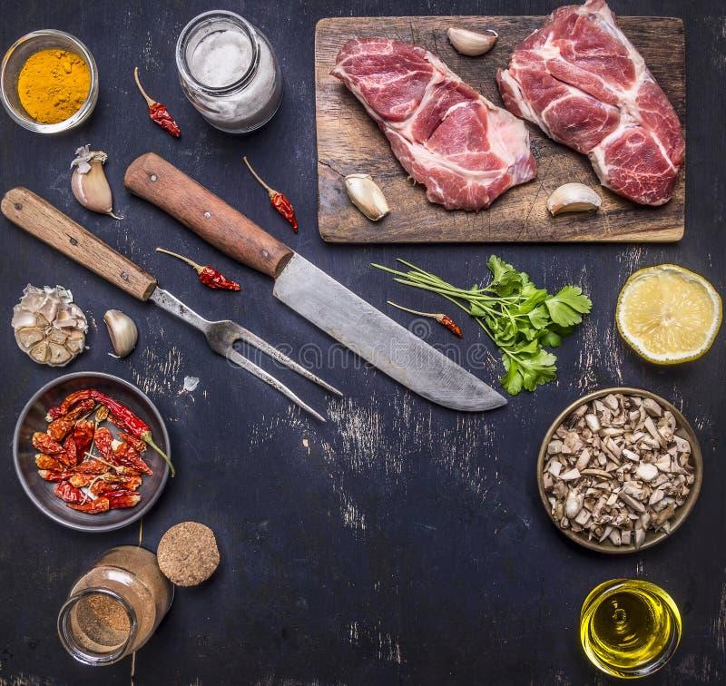 Ny rå grisköttbiff på en skärbräda med en kniv och gaffel för köttet med varma röda peppar, citronsmör på trälantligt royaltyfria bilder