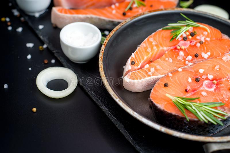 Ny rå improviserad fisklax eller forell, biffar, i en kastrull för att laga mat, med salt, peppar på svart stenbetong arkivbild