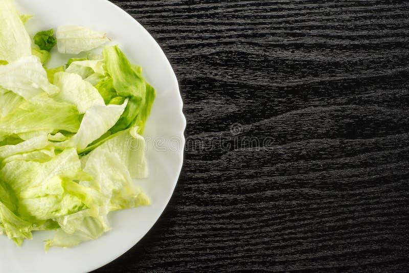 Ny rå isberggrönsallat på svart trä arkivfoton