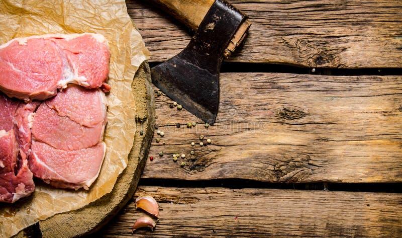 Ny rå köttfärs med en yxa arkivbild