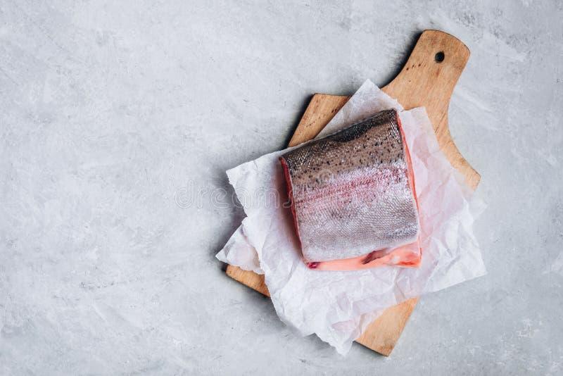 Ny rå lax eller forell för att laga mat på grå bakgrund arkivfoton