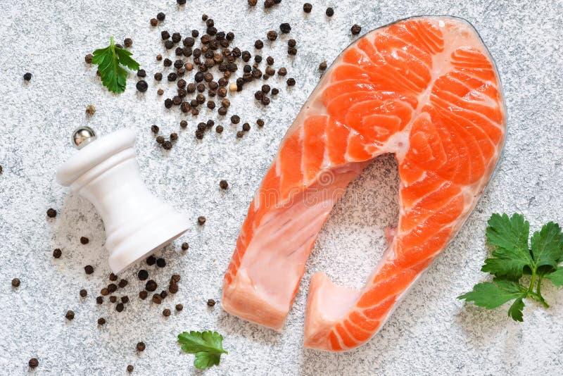 Ny rå lax och klassiska kryddor: salta peppar, citron på en vit konkret bakgrund ovanför sikt royaltyfri bild