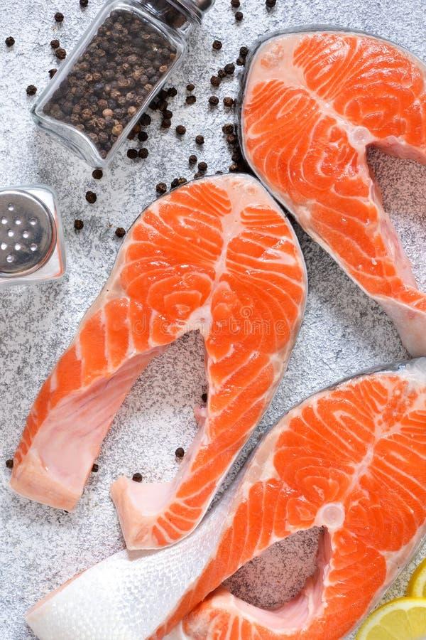 Ny rå lax och klassiska kryddor: salta peppar, citron på en vit konkret bakgrund ovanför sikt fotografering för bildbyråer