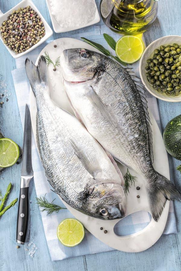 Ny rå matlagning för fisk för havsbraxen på svart stencountertop, bästa sikt arkivfoto