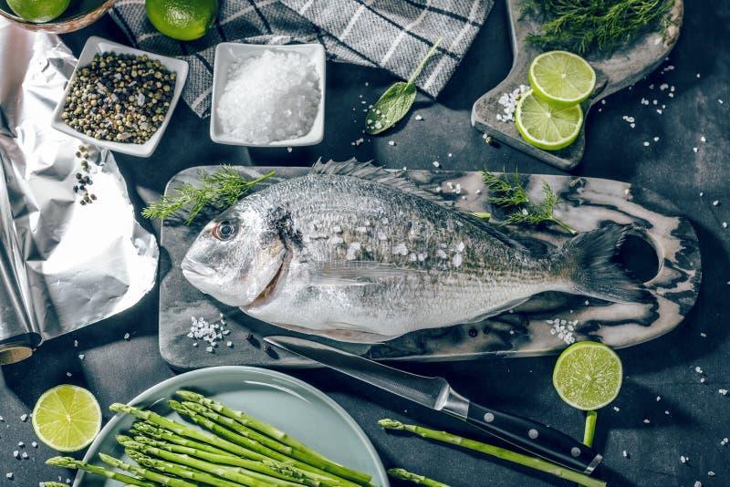 Ny rå matlagning för fisk för havsbraxen på svart stencountertop, bästa sikt royaltyfri fotografi
