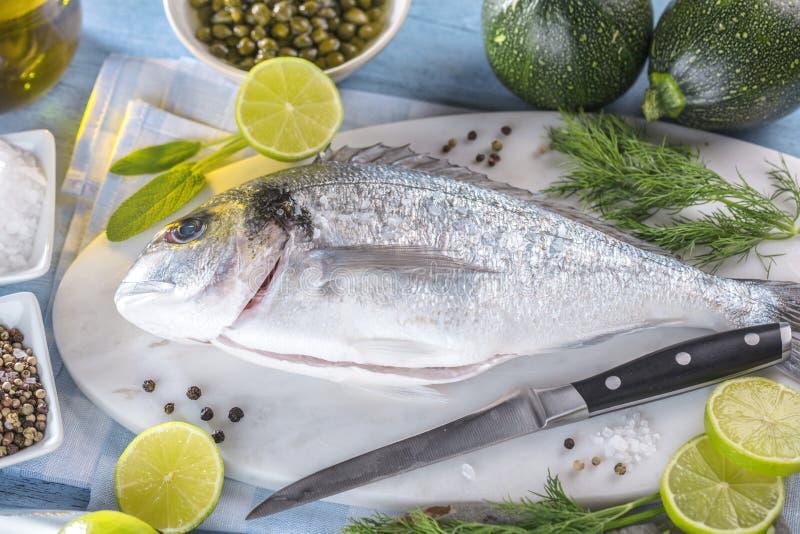 Ny rå matlagning för fisk för havsbraxen på svart stencountertop, bästa sikt arkivfoton