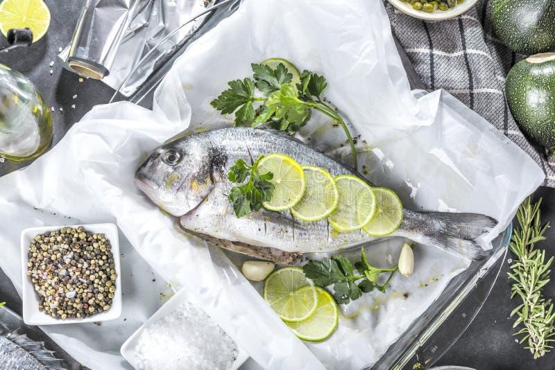 Ny rå matlagning för fisk för havsbraxen på svart stencountertop, bästa sikt royaltyfria bilder
