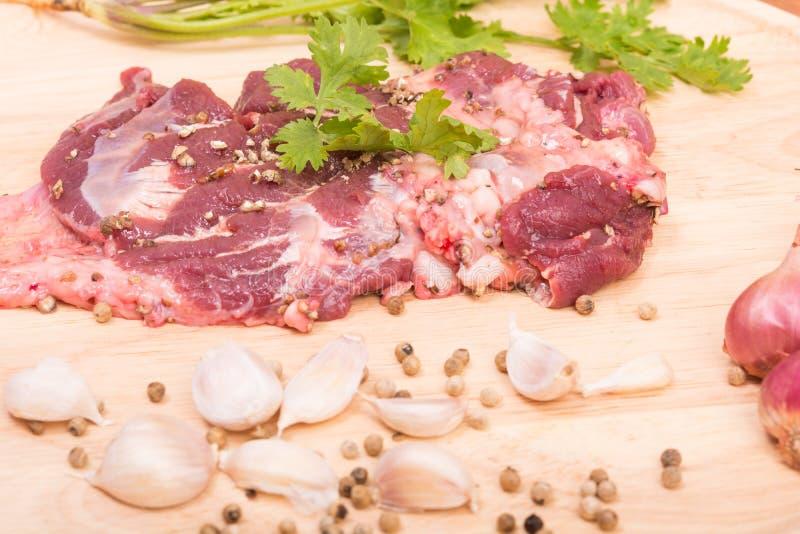 Ny rå nötköttköttskivor och vitlök, peppar på trä arkivbilder