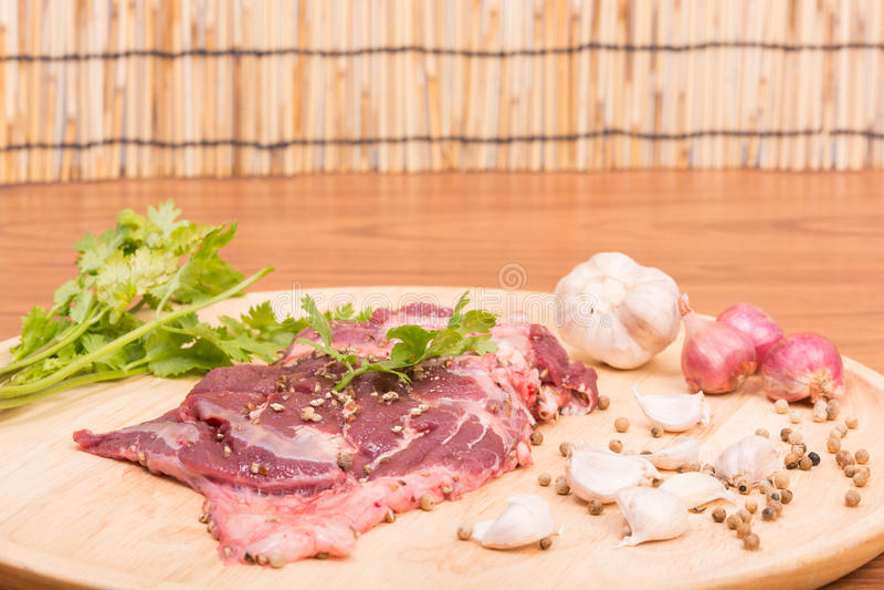 Ny rå nötköttköttskivor och vitlök, peppar på trä arkivfoton