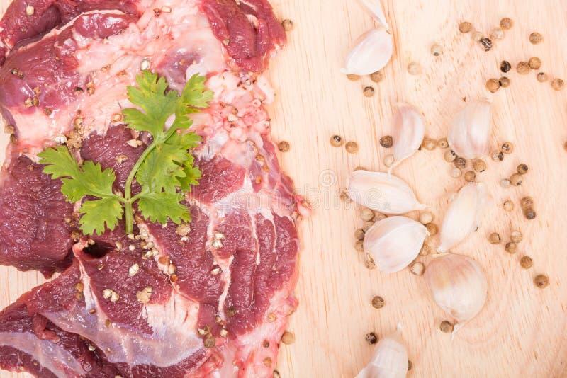 Ny rå nötköttköttskivor och vitlök, peppar på trä royaltyfria foton