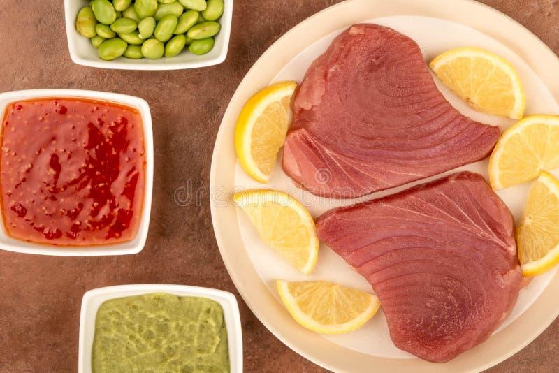 Ny rå okokt gul fena Tuna Steaks With Lemon Slices royaltyfri bild