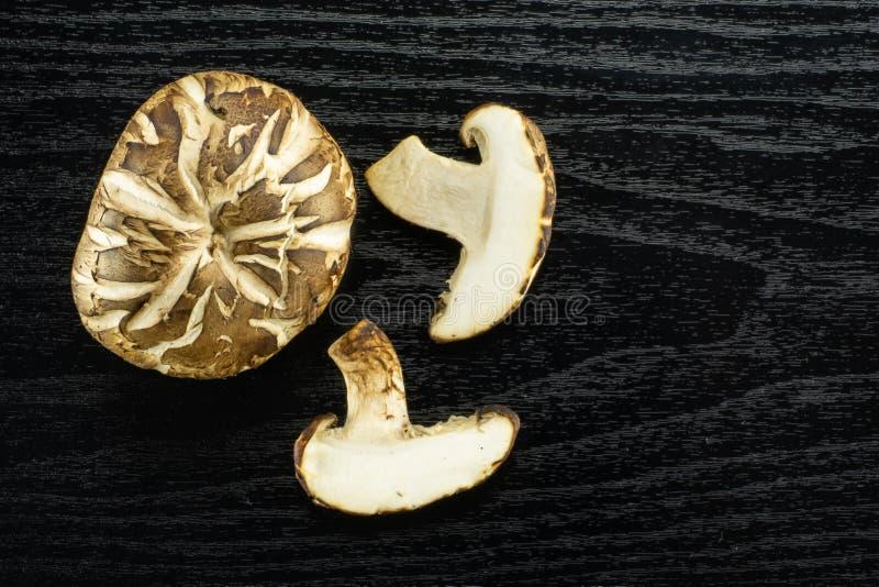 Ny rå shiitakechampinjon på svart trä arkivfoton