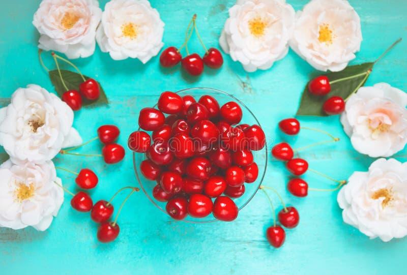 Ny röd körsbär i en bunke på en gammal målad trätabell med nya vita rosor som en ljus färgrik sommarbakgrund för arkivbild