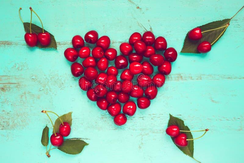 Ny röd körsbär i en form av en hjärta på en gammal målad trätabell som en ljus färgrik sommarbakgrund för säsongsbetonade kort, fotografering för bildbyråer