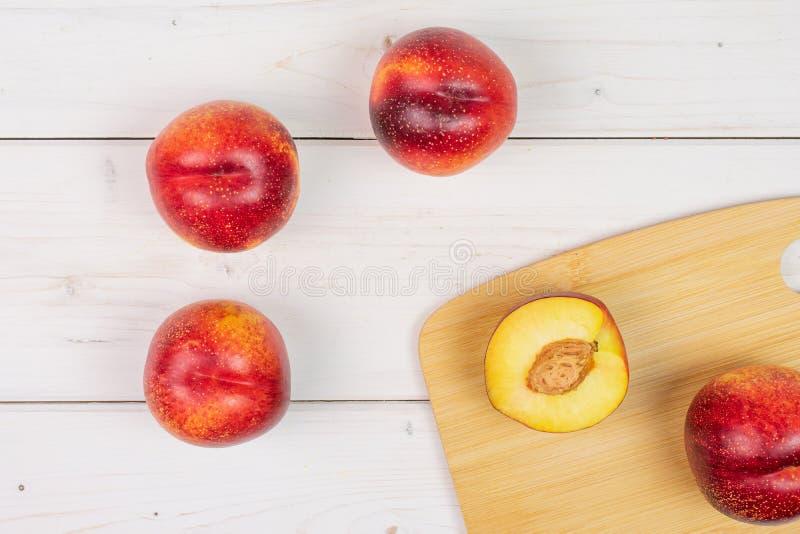 Ny röd nektarin på grått trä arkivbilder