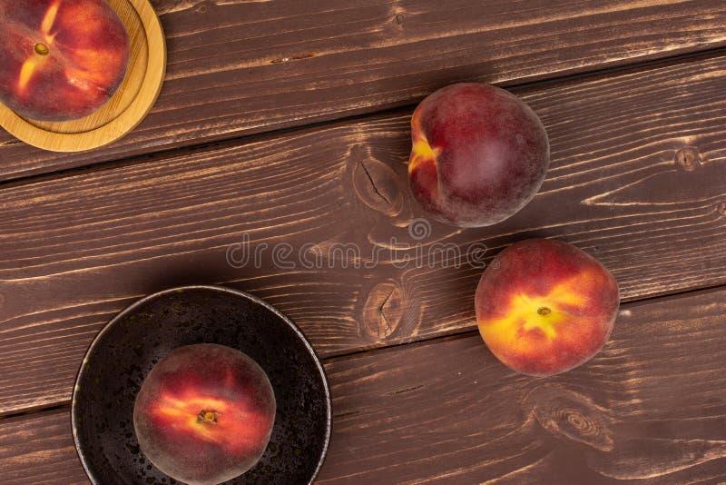 Ny röd persika på brunt trä fotografering för bildbyråer