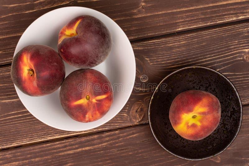 Ny röd persika på brunt trä royaltyfria foton