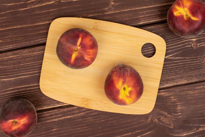 Ny röd persika på brunt trä arkivbilder