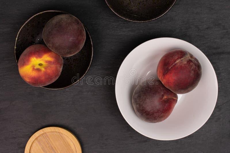Ny röd persika på den gråa stenen arkivfoto
