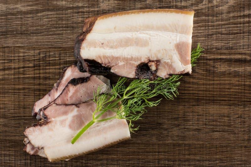 Ny rökt engelsk bacon på brunt trä arkivbilder