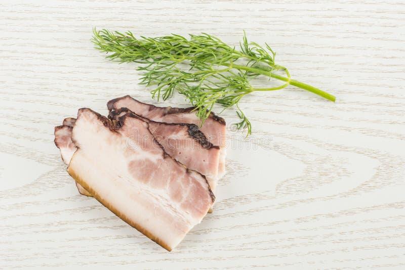 Ny rökt engelsk bacon på grått trä fotografering för bildbyråer