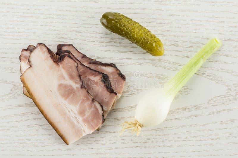Ny rökt engelsk bacon på grått trä royaltyfria bilder