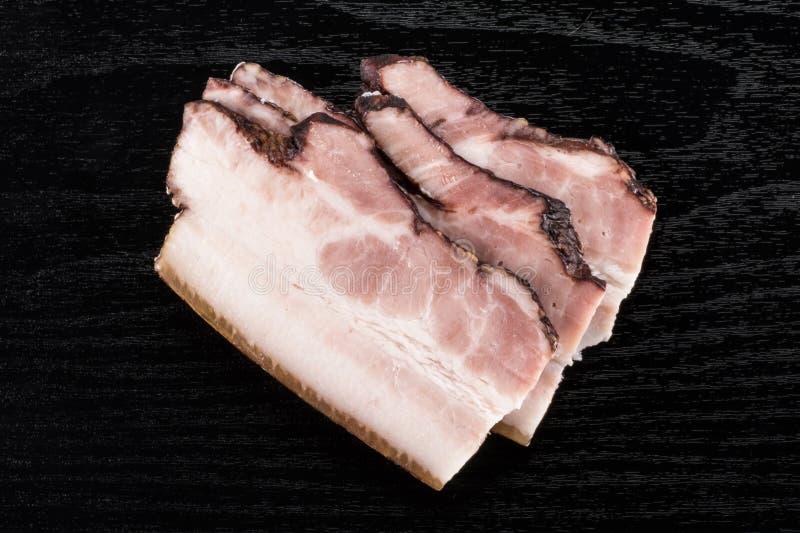Ny rökt engelsk bacon på svart trä royaltyfria bilder