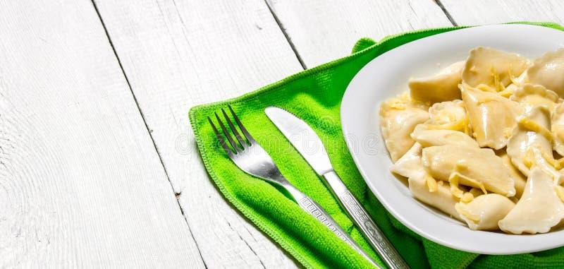 Ny ravioli med ost i plattan På vit träbakgrund arkivfoto