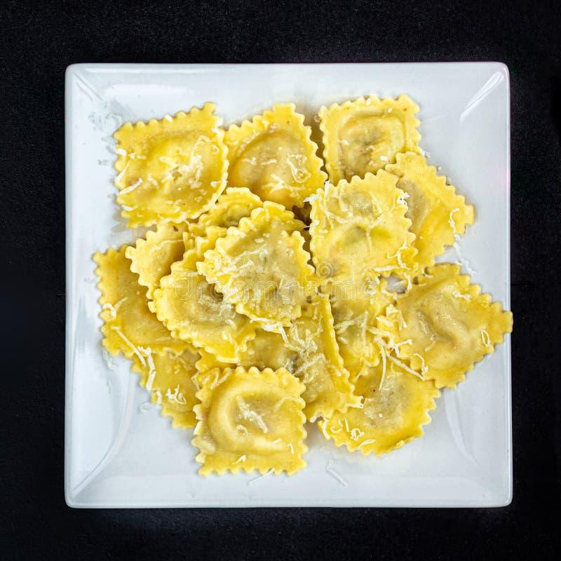 Ny ravioli på en vit platta över mörk bakgrund, bästa sikt ItalienareRaviolli slut upp kopiera avst?nd fotografering för bildbyråer