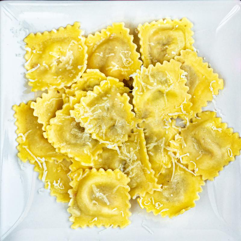 Ny ravioli på en vit platta över mörk bakgrund, bästa sikt ItalienareRaviolli slut upp kopiera avst?nd arkivbilder